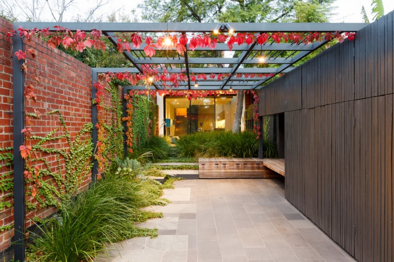 contemporary patio with concrete hardscaping red brick wall panel dark finish lattice wall shade with red vines and bulbs