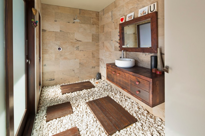 contemporary stone bathroom in warm beige small stone floors with wood pathways dark wood floating vanity raised white sink wood framed vanity mirror warm toned stone walls