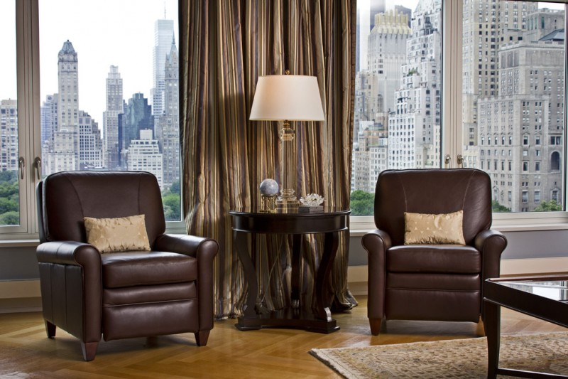 dark chocolate leather recliner chairs dark chocolate side table table lamp with white lampshade medium toned wood floors dark window curtain with gold accents