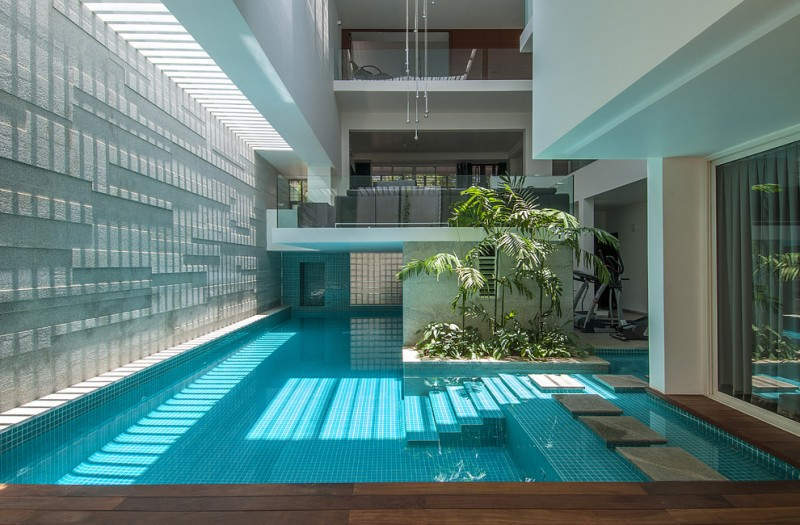 grand and superb modern indoor pool stone walls longer skylight with metal bars concrete pool's steps concrete pool's pathway