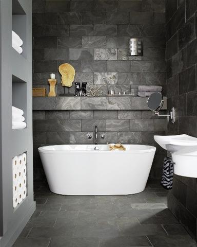 gray granite wall gray concrete wall gray tiled floors white bathtub some recessed shelves