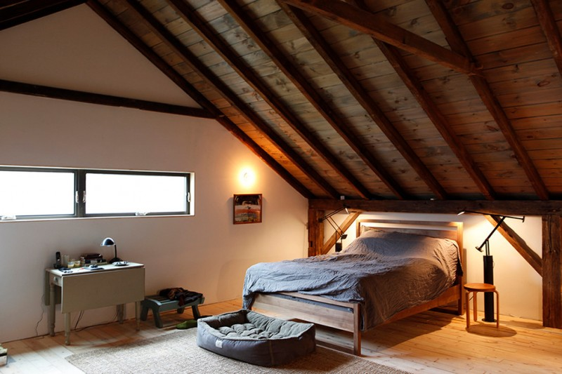 high arched ceiling bedroom with wood siding roof and solid wood supports drop leaf console table wood bed frame