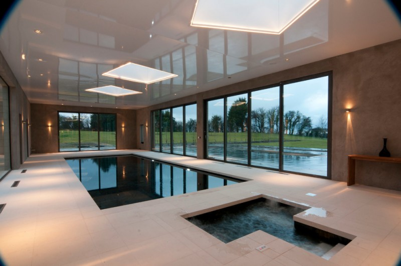 large modern indoor swimming pool white hardscape floors clean lined pool small jacuzzi large ceiling lamps large glass windows