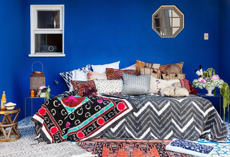 modern Bohemian bedroom idea bold blue wall color many textural ethnic pattern bedding mutlicolored ethnic carpet