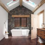 Modern Bathroom Design With Exposed Dark Stone Wall And Shuttered Window Arched Ceiling Skylights Exposed Wood Ceiling Beams Dark Wood Floors