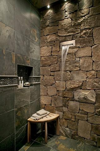 modern bathroom idea natural stone wall dark tiled floors and walls corner wood bench waterfall shower head
