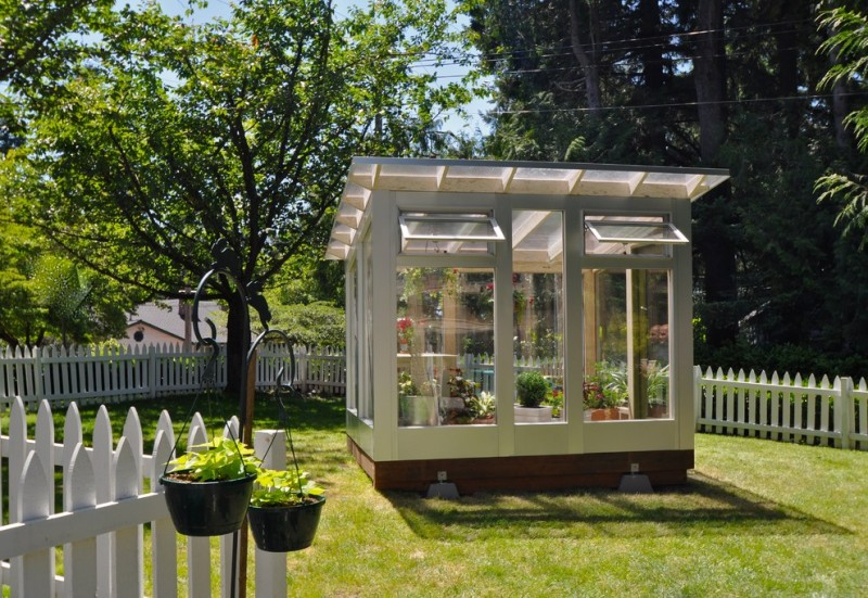 modern greenhouse shed with large glass windows and operable upper windows
