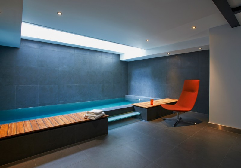 modern indoor pool with dark shade wooden bench red lounge chair skylight some recessed lamps