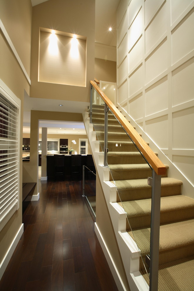 modern interior stair with temper glass railing and wooden banister on top