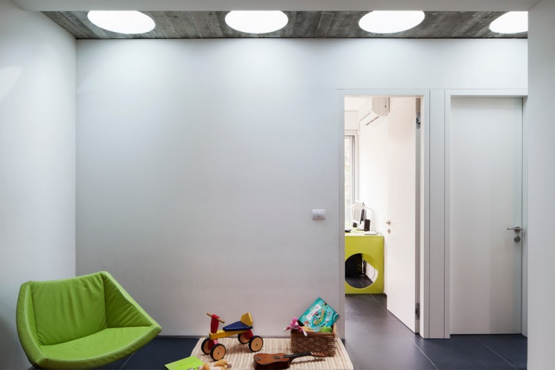 modern kids playground with higher ceilings accented with tubular skylights green lemon chair dimmer black tiles flooring