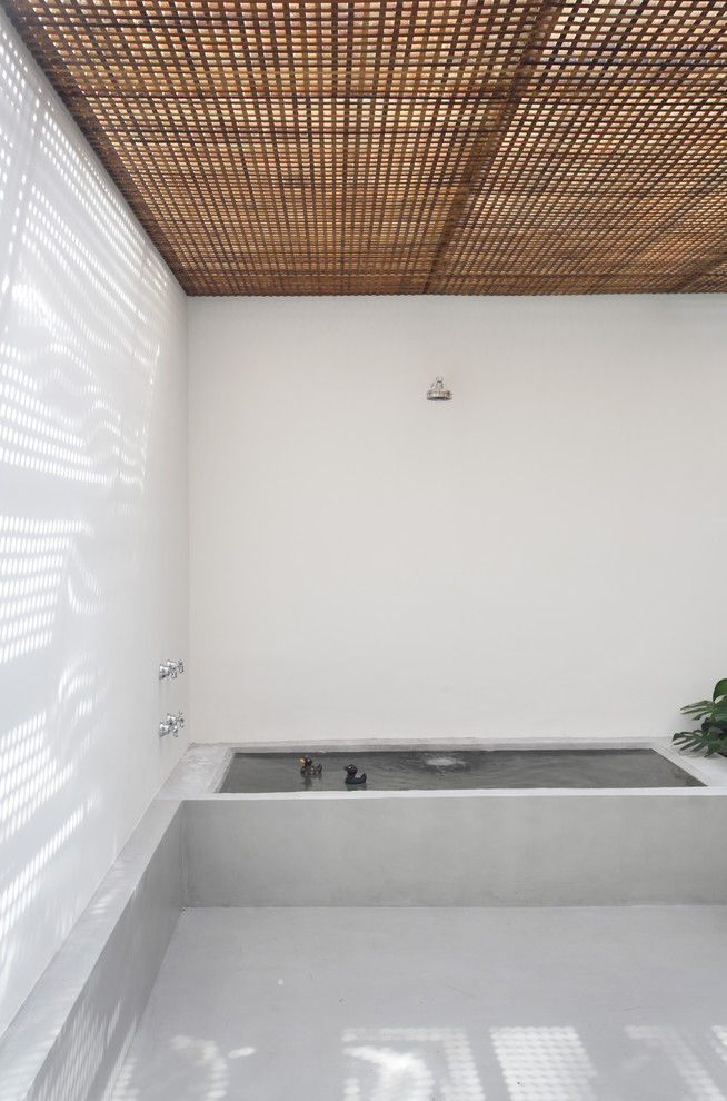 modern minimalist bath rectangular concrete tub clean lined walls and floors wooden muxarabie ceilings