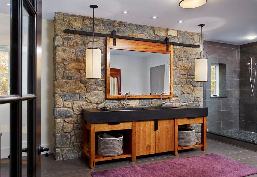 modern rustic bathroom design stone wall wood bathroom vanity with black countertop wood framed mirror purple rug gray tiled floors