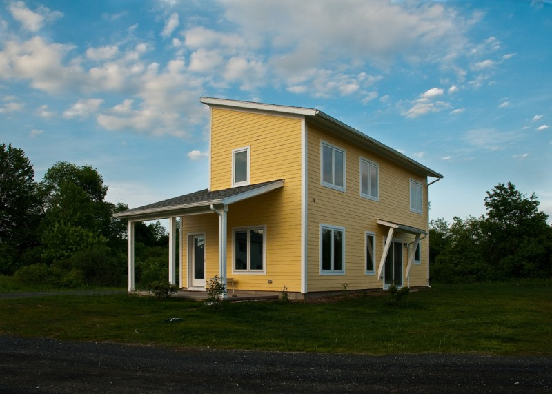 pop of yellow farmhouse exterior in modern style sloping shed roof enclosed patio lots of windows with white trims