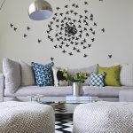 Simple And Small Living Room White Painted Wall Accented With A Cluster Of Paper Cut Black Birds Modern Floor Lamp With Metal Lampshade Modern Poufs Monochromatic Area Rug