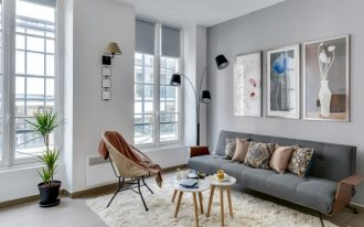 simple modern living room in grey grey mid century modern sofa modern floor lamps with black lampshades mid century modern chair and tables white shag rug