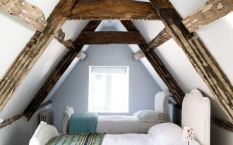 small attic bedroom for twin kids classic styled twin beds in white turquoise rug exposed wood ceiling beams white wall and floor