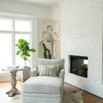 Small Modern Living Room White Brick Wall With Modern Recessed Fireplace Medium Toned Wood Floors Light Gray Recliner Chair Striped Throw Pillows Light Cowhide Area Rug White Round Top Side Table With