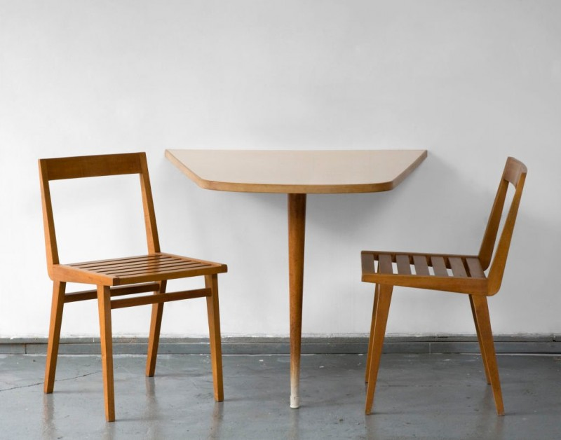 wall mounted table in asymmetric shape and with single pointed leg a pair of wood dining chairs