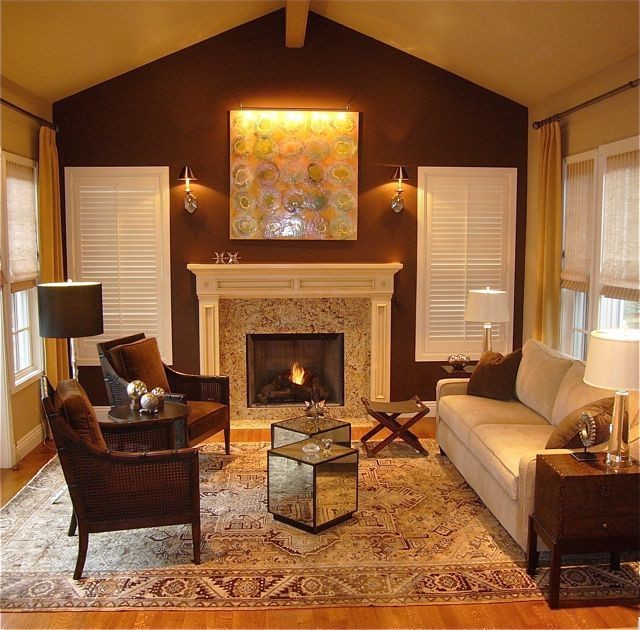 warm & inviting tan living room idea dark brown painted wall color artistic wall art standard fireplace white window shutters mirrored cube tables light cream couch dark brown chairs medium toned wood