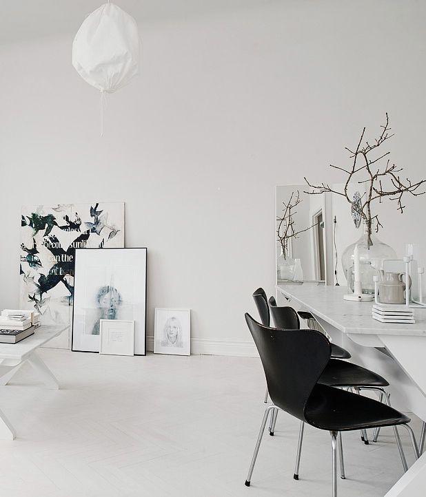 white interior Scandinavian idea monochromatic artworks black scandinavian chairs longer white table frameless mirror