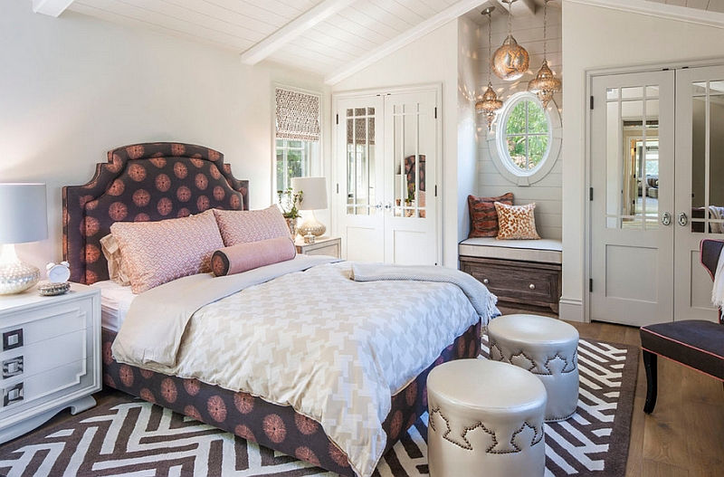 Moroccan style bedroom with modern twist dark toned bed frame with headboard and pink accents silver toned ottomans modern style rug white bedside tables gold toned Moroccan pendants