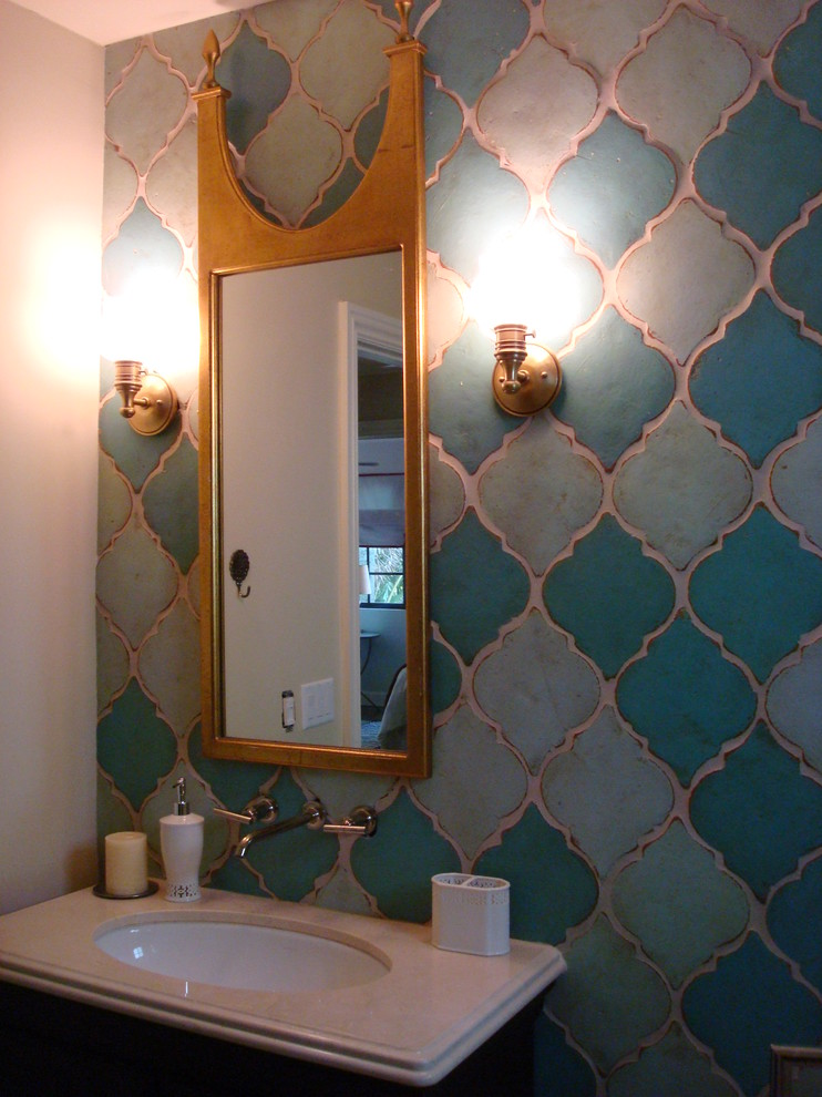 Moroccan style tiles wall small bathroom vanity white undermount sink and white countertop a couple of vanity lamps vanity mirror with gold frame