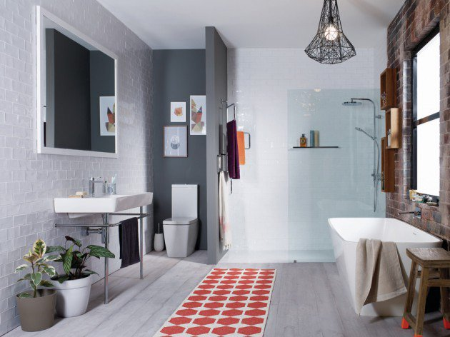 Scandinavian bathroom design dominated by light gray shade light gray subway tiles wall light gray wood planks floors freestanding sink white framed mirror run rug with orange motifs