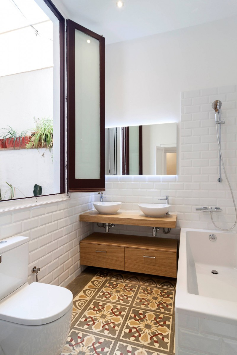 Scandinavian bathroom patterned tiles flooring wall mounted toilet in white built in bathtub frameless mirror light wood vanity with flat paneled cabinets a couple of white sinks white subway til