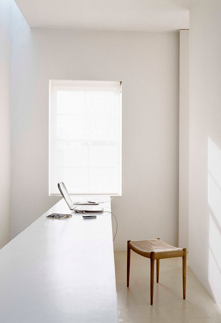 Scandinavian workspace idea central glass window long white working desk single wood bench with pointed legs white walls white floors