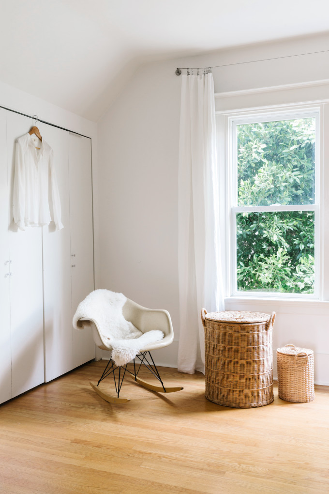 airy and bright bedroom idea a rocking chair with fury blanket natural fiber baskets for side tables light wood floors white curtains recessed closet in white