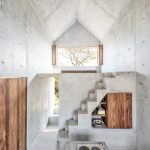 Concrete Living Space With Wood Element Concrete Kitchen Counter Recessed Open Shelves Attic Roof Glass Window