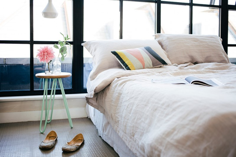 contemporary bedroom idea white bedding treatment colorful pillow tiny side table with round wood top and blue hairpin legs