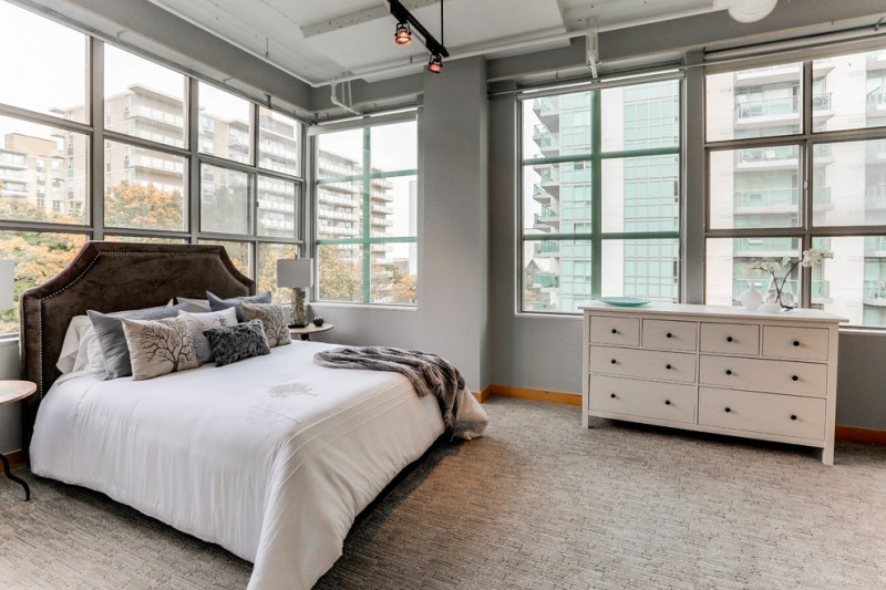 contemporary bedroom with gray shade gray wall glass windows with trims gray carpeted floor white dresser