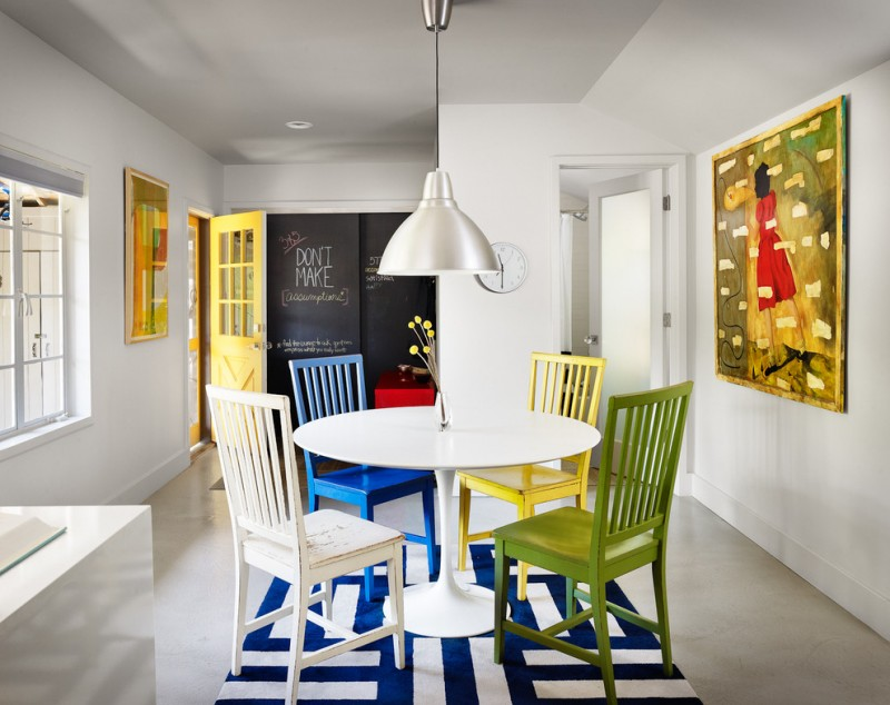 contemporary dining nook colorful wood dining chairs blue white rug pendant with silver lampshade chalkboard wall yellow door