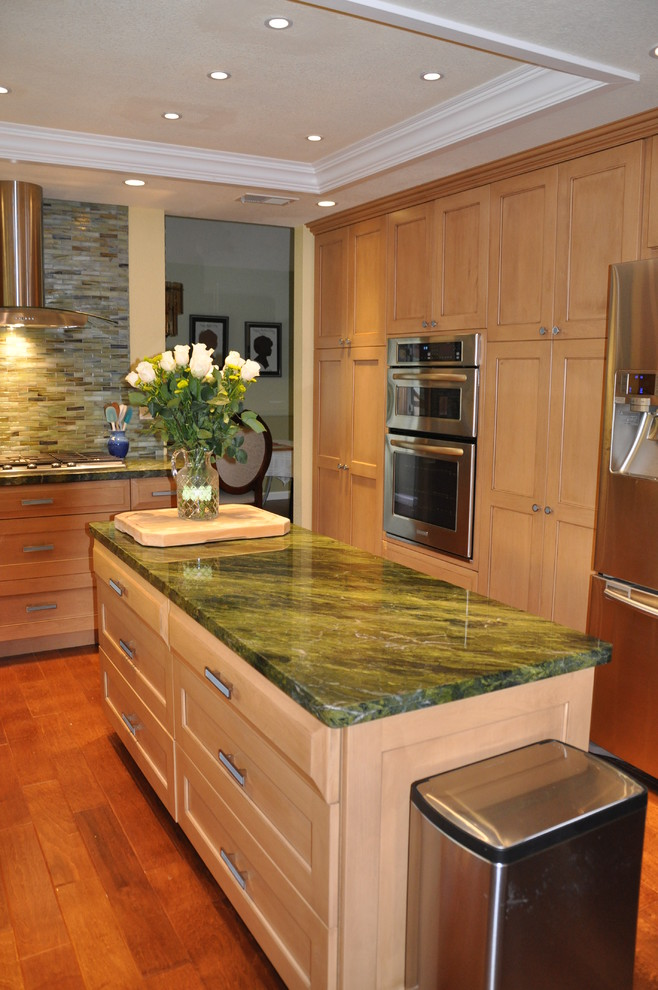 contemporary kitchen island with green marble countertop and raised panel cabinets in white wood floors
