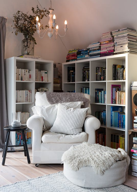 cozy reading nook white armchair with blanket and striped throw pillow ottoman table in white black painted wood side table bookshelves in white white chandelier