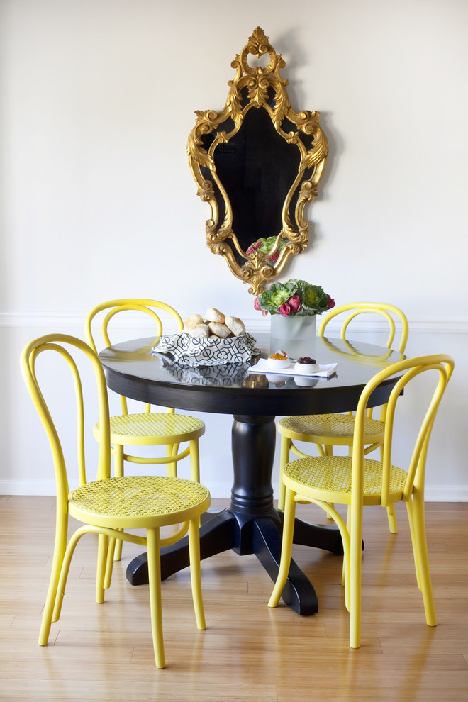 eclectic dining room vintage wall mirror with gold handcrafted frame pop of yellow dining chairs black painted dining table with round top light wood floors