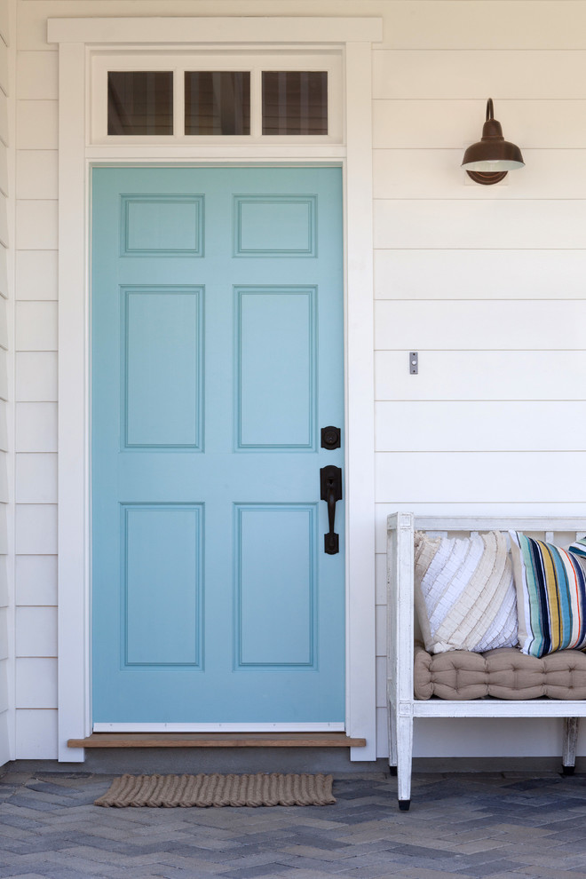 farmhouse exterior idea blue front door white wood siding exterior walls white wood seat with throw pillows and layered mattress concrete floors brown door mat