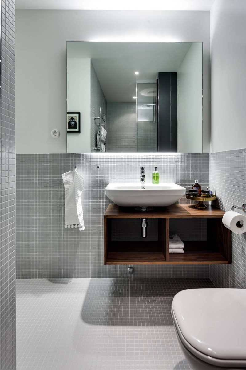 gloomy Scandinavian bathroom gray mosaic tiled walls large frameless mirror floating wood vanity with open shelves white sink wall mounted toilet gray mosaic tiled floors