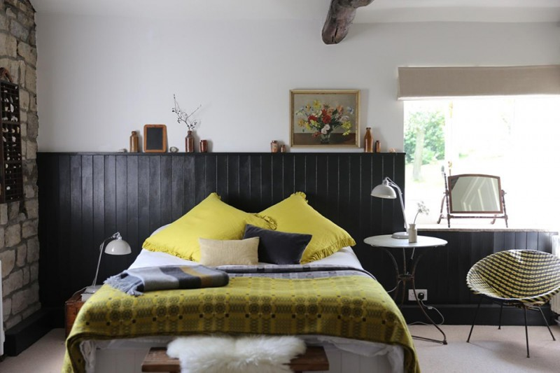 guest bedroom idea black wood planks background wall white concrete wall yellow bedding treatment yellow pillows natural stone walls modern yellow black chair