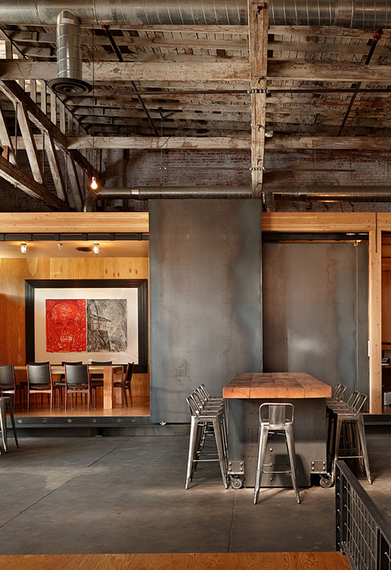 industrial style open concept dining room dark finished walls and floors hardwood dining table metal bar stools exposed metal beams and ceilings