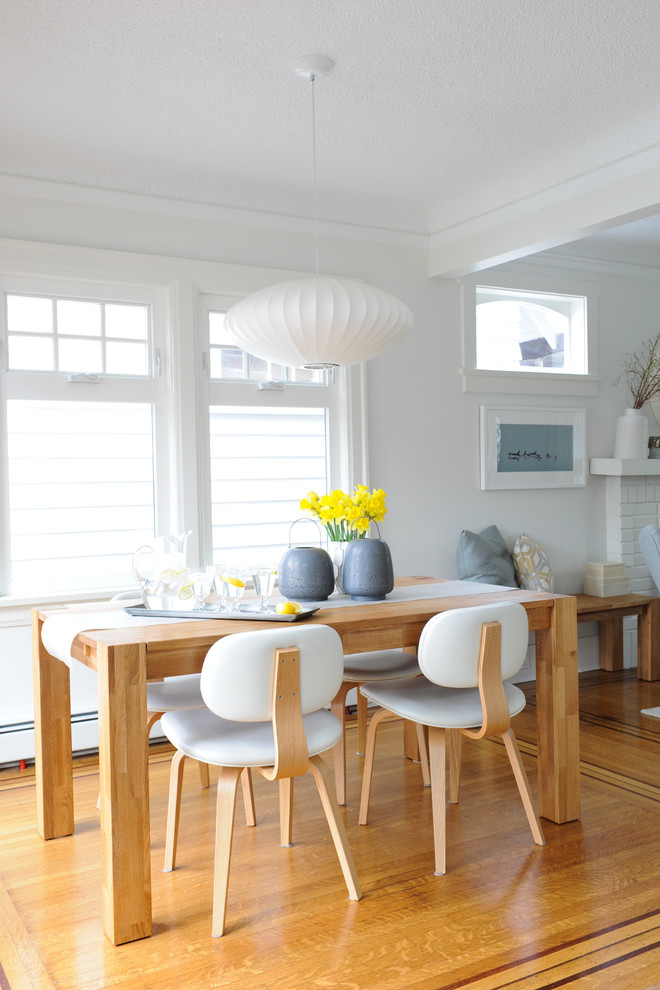 mid century modern dining room light wood floors white walls huge pendant with white lampshade light wood dining table and chairs