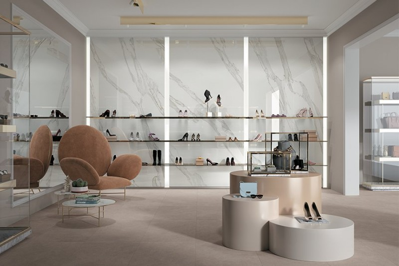 modern and luxurious display shoes room with marble wall beige carpeting floors bold beige chair some display tables