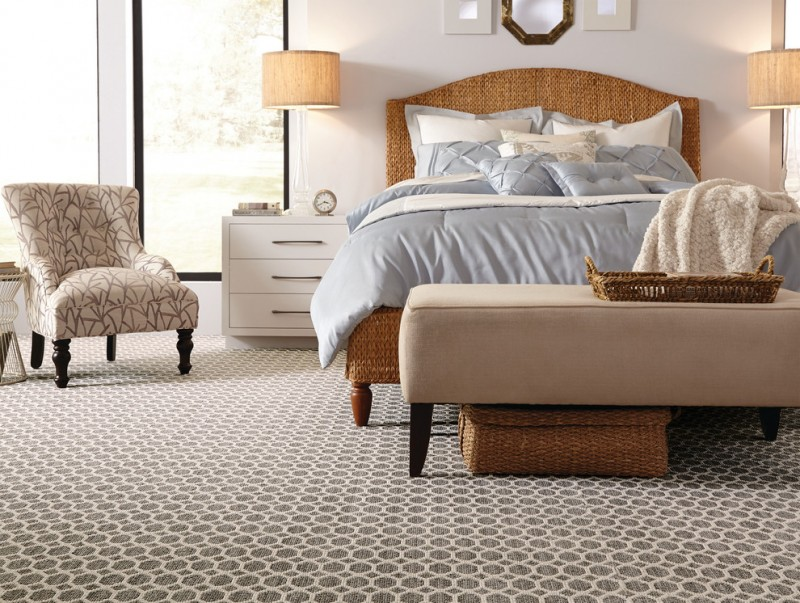 modern bedroom design hex patterned modern carpet in gray woven bed frame with headboard white bedside table with drawers armchair