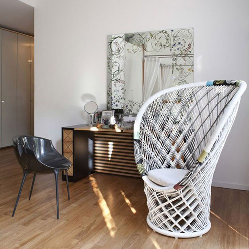 modern bohemian powder room wood vanity mirror with decorative floral motifs white wicker black vanity chair light wood floors