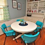 Modern Vintage Dining Space Round White Top Dining Table In White Metal Dining Chairs With Radiant Blue Finish Medium Toned Wood Floors Blue Walls White Baseboard Multicolored Curtains White Wind