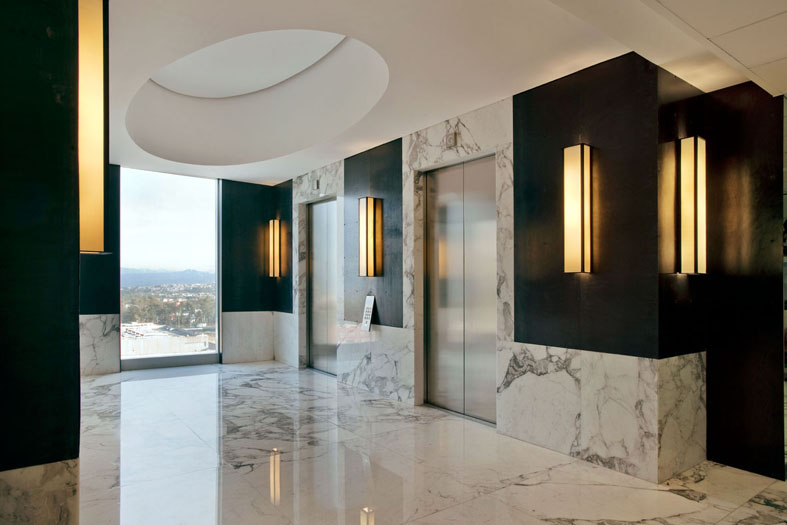 office lounge idea white Italian marble floors and walls black panelling yellow lighted wall lamps in modern style