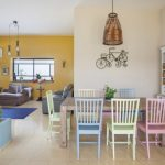 Open Concept Dining Space Rainbow Pastel Dining Chairs Wood Dining Table Light Cream Tiled Floors Yellow Wall Light Yellow Wall Gray Sofas
