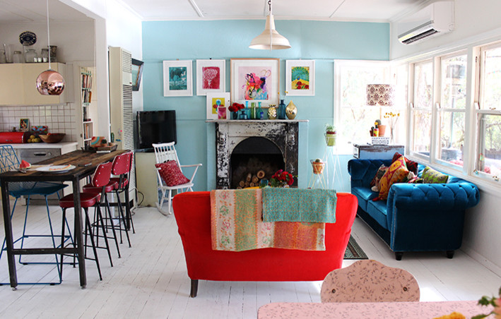 open concept living room in modern bohemian style light blue wall white trimmed windows red sofa blue sofa white rocking chair shabby black fireplace