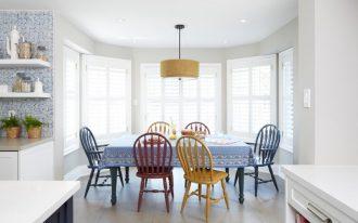 rainbow dining chairs large rectangular dining table with blue skirt pop of yellow pendant white ceramic tiled floors white walls mosaic tiled backsplash
